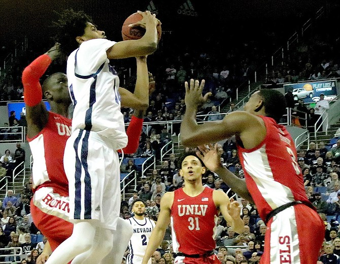 Lindsey Drew (11) takes a jump shot in a sea of red against UNLV last season at Lawlor Events Center.
