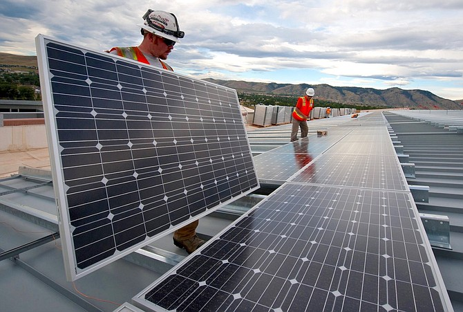 Great Basin Solar staff members install solar panels on a large commercial building. The Reno company saw its revenue increase by roughly 25% in 2020 due to a renewed appeal for home-owners and businesses.