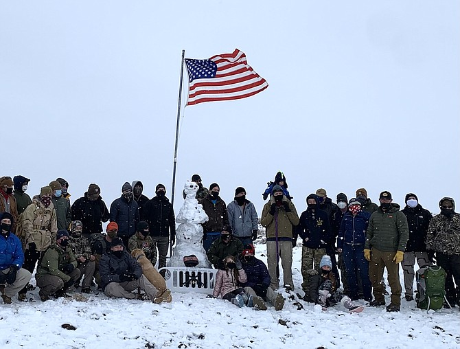 Chief petty officer selectees and their mentors bundle up on SAR (Search and Rescue) Mountain on Dec. 7 to swap out the U.S. flag and place a memorial rock.