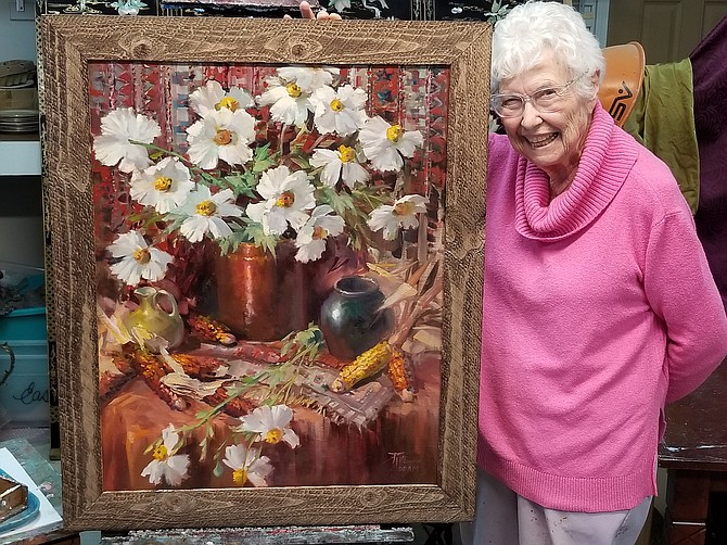 Artist Joyce Pike with the painting she's donating to the Sage Hens Scholarship Raffle.