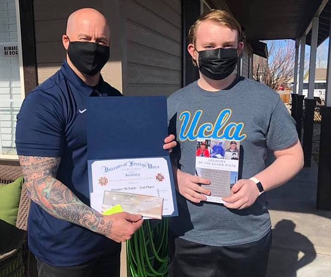 Oasis Academy counselor Andy Lenon, left, presents the second-place certificate for the Veterans of Foreign Wars Post and its Auxiliary patriotic audio essay competition to Hunter McNabb.