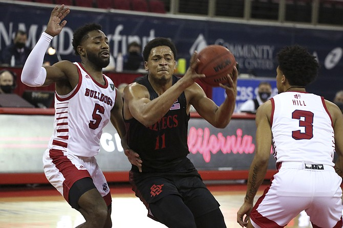 San Diego State's Matt Mitchell drives past Fresno State's Jordan Campbell, left, and Isaiah Hill during Thursday's game in Fresno, Calif. (AP Photo/Gary Kazanjian)