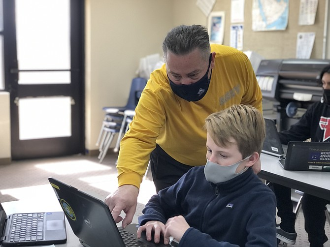 Carson High School's NJROTC instructor Chief Dan Ingram helps sophomore Luke Syndergaard learn to navigate through a virtual orienteering course using an avatar to use a compass and climb topographic maps to reach pre-determined checkpoints and destinations.
