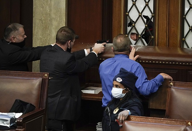 Police with guns drawn watch as rioters try to break into the House Chamber at the U.S. Capitol on Wednesday, Jan. 6, 2021, in Washington. (AP Photo/J. Scott Applewhite)