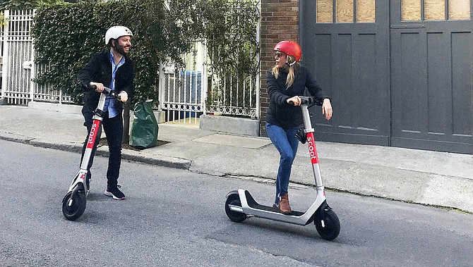 A couple uses Bird scooters in San Francisco in this media photo.