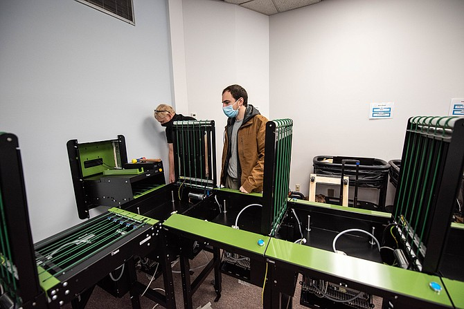 Photo: Nevada Momentum Fueled by RAD Jesper Edwards and Ove Linden, Lyngsoe Field Support Engineers, install an automated materials handler at the Carson City Library in December.
