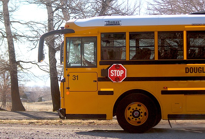A Douglas County school bus picks up children in Genoa on Tuesday.