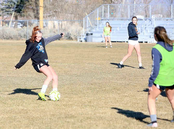 Douglas senior Kamryn Harper takes a shot during practice Thursday afternoon while fellow senior Kennedy Cole watches on.