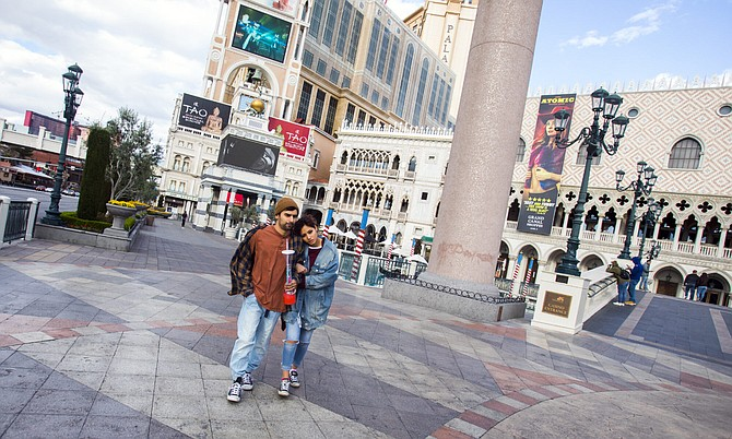 A couple walks past the Venetian on Tuesday, March 17, 2020, the same day Gov. Steve Sisolak orders casinos to shut down temporarily because of the pandemic.