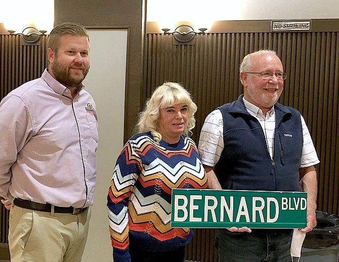 Minden Town Manager JD Frisby presents a street sign to Carol and Matt Bernard. Matt spent a decade on the town board before resigning his seat earlier this year.
