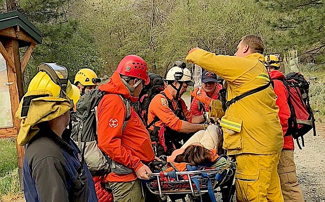 Rescuers from East Fork Fire Protection District and Douglas County Sheriff's Search and Rescue aid a hiker on a Genoa trail last summer.