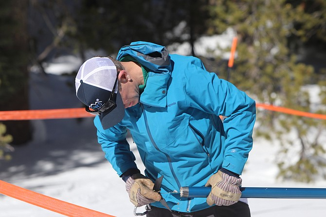 Hydrologist Bill Anderson of the Natural Resources Conservation Service checks the bottom of a cylinder for snow and dirt before weighing the content.