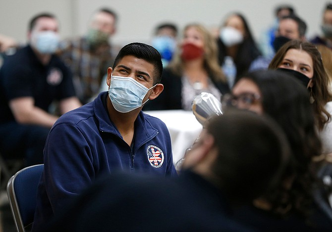 Western Nevada College Paramedicine Program Coordinator Terry Mendez, left, congratulates Joshua Adams during a graduation ceremony for the first cohort of the paramedic program Feb. 20 in Carson City.