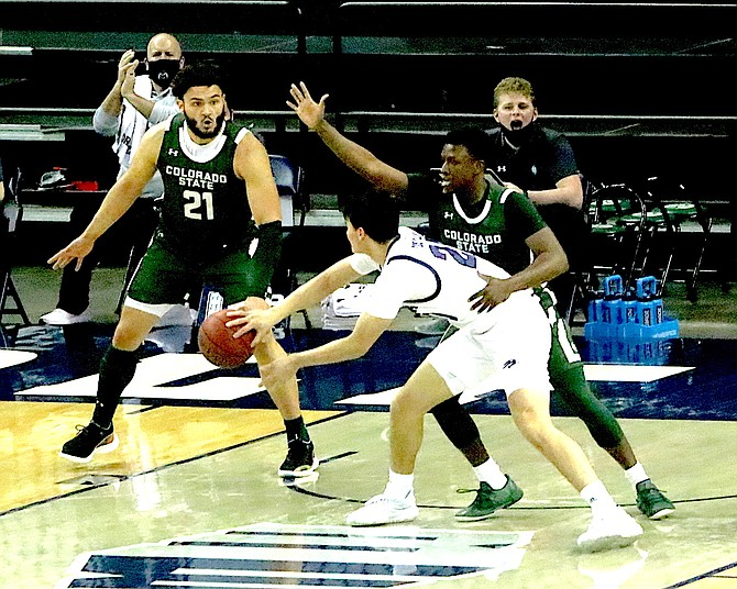 Nevada guard Daniel Foster (20) passes around the Rams Isaiah Stevens (4) in the first half of Friday's Nevada-Colorado State men's basketball game at Lawlor Events Center.