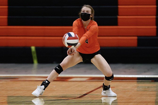 Douglas High's Caitlyn Stephens drops down to bump a ball against Reno High Thursday night. The Tigers fell in their home opener against the Huskies, but look to bounce back against Carson Tuesday