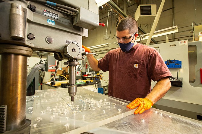 A Tripp Enterprises employee drills holes in acrylic at the manufacturing company's facility in Sparks.