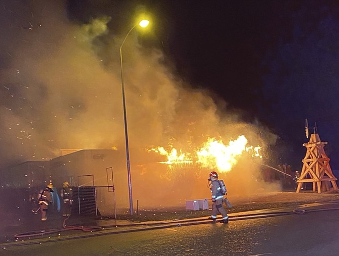 Wind-driven flames threatened to spread to neighboring businesses early Saturday morning.