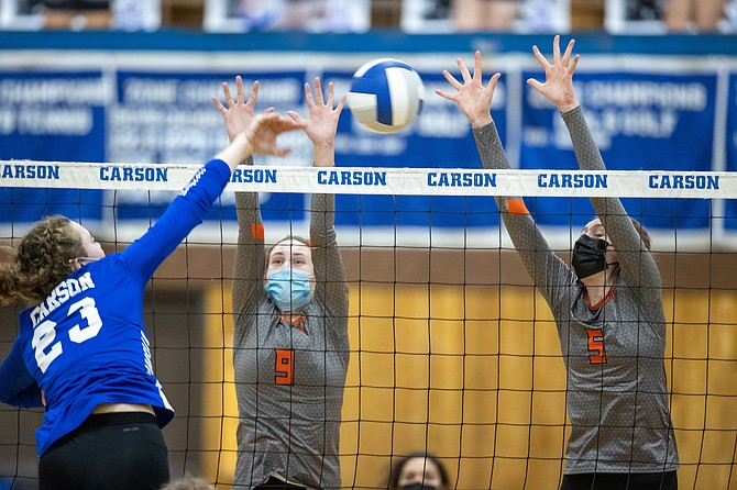 Douglas High's Chana Rothschild (9) and Marin Collins (5) go up for a block on Carson outside hitter Cami Larkin.