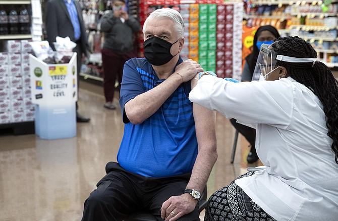 Gov. Steve Sisolak gets the Johnson & Johnson COVID-19 vaccine from Trashelle Miro, pharmacy manager, at an Albertson's supermarket pharmacy in Las Vegas on Thursday. (Photo: Steve Marcus/Las Vegas Sun via AP)