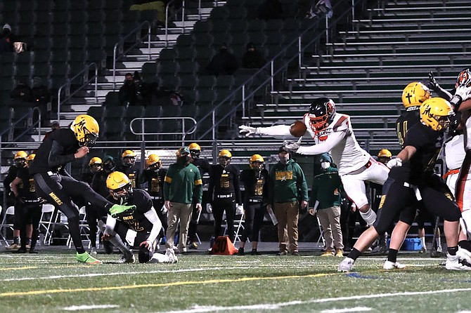Douglas High senior captain Brady Dufloth comes around the left edge and blocks a Bishop Manogue field goal attempt Friday night. It's the second kick the Tigers' special teams has blocked in as many games so far this season.