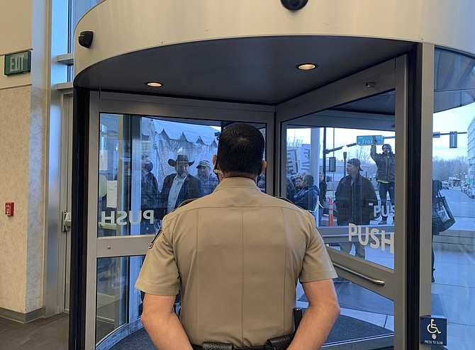 Anti-government activist Ammon Bundy, wearing a cowboy hat, yells through the closed Ada County Courthouse door at law enforcement officers inside Monday in Boise, Idaho. (AP Photo/Rebecca Boone)