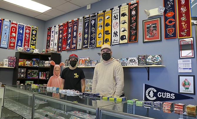 Lance Lucha, right, and his son Deion, stand inside Ball Hogs Sports Collectibles and More on Kietzke Lane in Reno, which saw revenue double in 2020 compared to 2019 thanks to the pandemic.