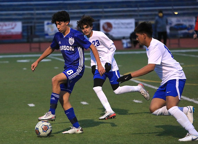 Luis Carrillo stands over the ball as he is crowded by two Reed defenders Wednesday night. Carrillo scored his first two varsity goals in helping the Carson boys soccer team defeat the Raiders, 3-2.