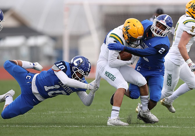 Carson High's Javier Arellano Barrios (2) and Salvador Mora-Rodriguez (10) tackle Bishop Manogue's Michael Schneider on Friday at Carson High.