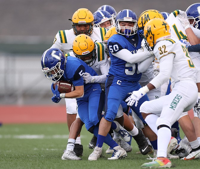 Carson High's Jacob Campbell fights through a pile of Bishop Manogue defenders Friday night. Carson football had its Friday night game with Galena canceled due to COVID. The Senators will now play Spanish Springs Saturday at 1 p.m.