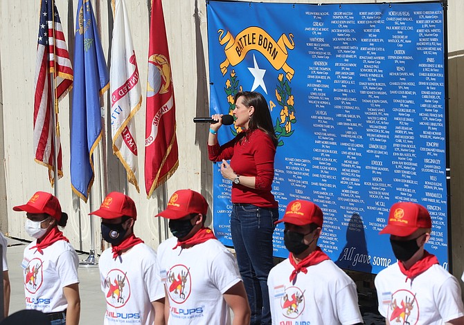 "Standing in front of a Nevada flag with the names of those from the Silver State who were killed in Vietnam, singer Kimberly Dixon leads the audience in ""God Bless America"" at the conclusion of the National Vietnam War Veterans Day. Members of the Devils Pups line up in front. (Photo: Steve Ranson/LVN)"
