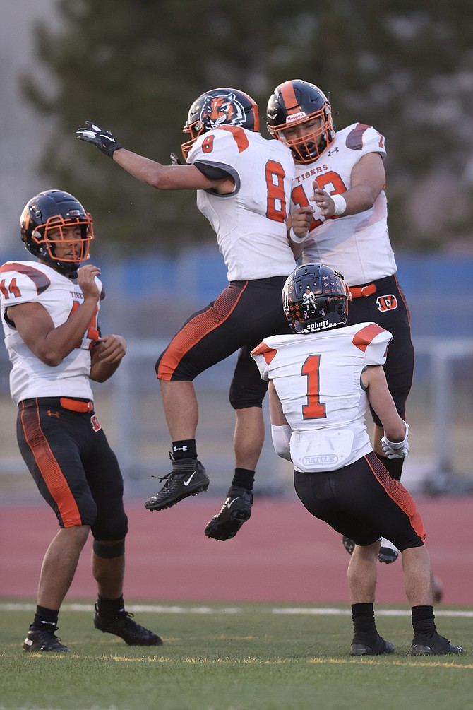 Douglas High's Trevor Kruger (8) and Gabe Foster (13) jump into the air to celebrate a touchdown in the Tigers' 38-9 win over Carson Friday night.