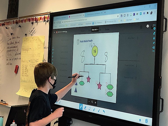 A Pau-Wa-Lu Middle School student uses one of the new digital whiteboards.