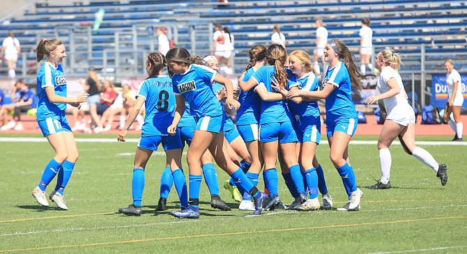 The Carson High girls' soccer team celebrates around Alyssa Tomita, who scored the game-winning goal for the Senators in the 74th minute against Reno Saturday.