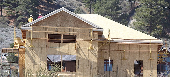 Workers build a house near Jacks Valley Road on Tuesday afternoon.