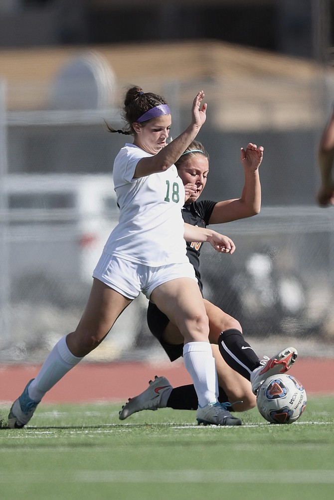 Douglas High's Helene Henry-Greard slides in on Bishop Manogue's Emmery Kate Guillen during the first half of a Class 5A regional quarterfinal contest between the Tigers and the Miners. Douglas won 3-0 and will play McQueen Thursday afternoon at 4 p.m.