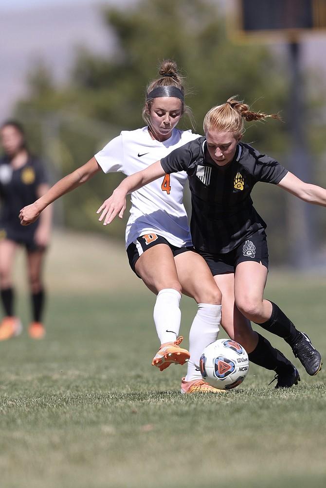 Kylee Lash (4) of Douglas High girls' soccer tries to get around a Galena defender Saturday.
