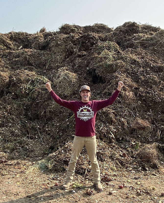 Cody Witt with a big pile of green waste recycled during 2020 into a range of soils and mulches. Full Circle Compost Photo