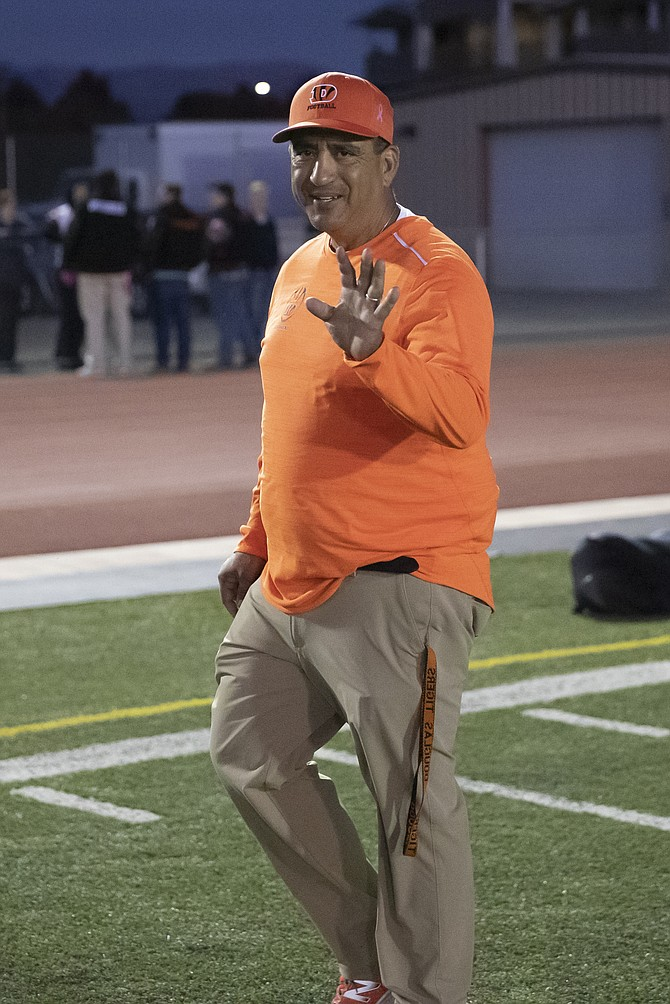 Douglas High football coach Ernie Monfiletto waives as he walks his home sideline prior to kickoff on a Friday night.