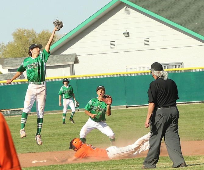 Brady Alves (18) of Fallon reaches high to prevent the ball from going into the outfield as Fernley's Brandon McCullar reaches second. Also involved with the play is Greenwave second baseman Francisco Tapia (4). Fallon won the first game against Fernley in the three-game series. (Steve Ranson/LVN)
