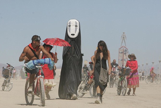 Burning Man participants walk on the playa at the Black Rock Desert near Gerlach on Aug. 28, 2008. (Photo: Brad Horn/AP, file)
