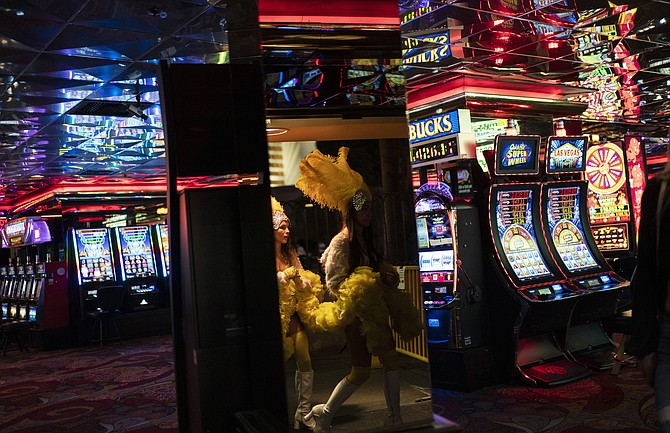 Buskers dressed as showgirls walk into a casino along the Las Vegas Strip on Feb. 10. For the first time since the pandemic began, Nevada's gaming win exceeded $1 billion in March. (Photo: John Locher/AP, file)