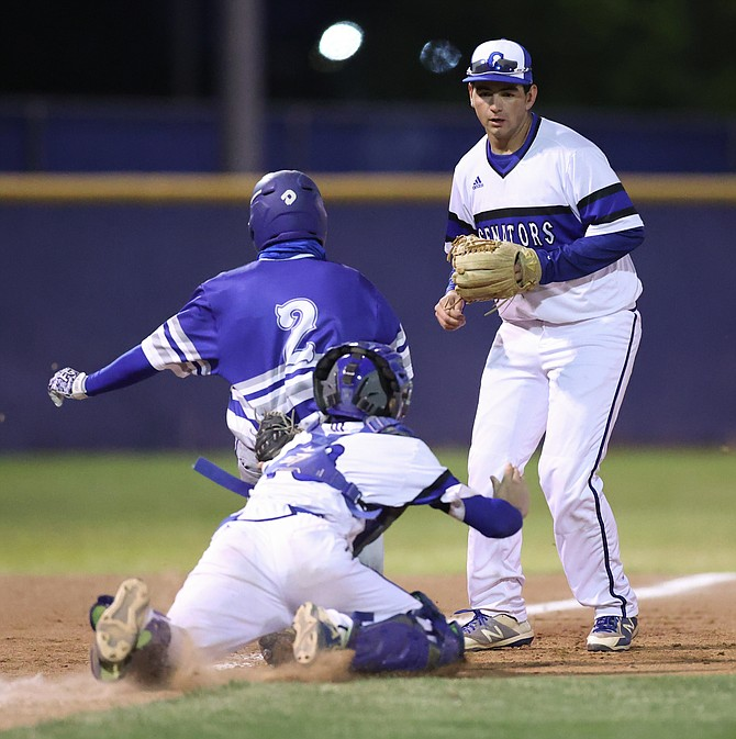 Carson High catcher Bryce Baker dives to tag McQueen's Reece Davis during a Class 5A league game between the Carson Senators and the McQueen Lancers at Carson High School Tuesday night.