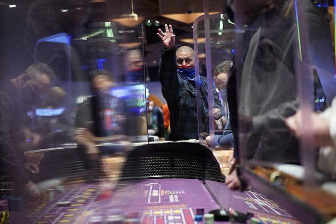 People play craps while wearing masks and between Plexiglas partitions as a precaution against the coronavirus at the opening night of the Virgin Hotels Las Vegas on March 25. (Photo: John Locher/AP)