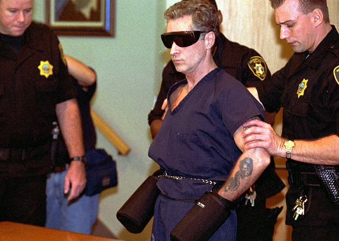 Death row inmate Patrick McKenna is escorted into district court under tight security to decide where his death penalty hearing will be held on Aug. 3, 1996, in Las Vegas. (AP Photo/Jack Dempsey)