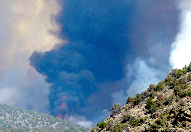 Flames can be seen glowing through the black smoke from the Numbers Fire burning in the Pine Nut Mountains in July 2020.
