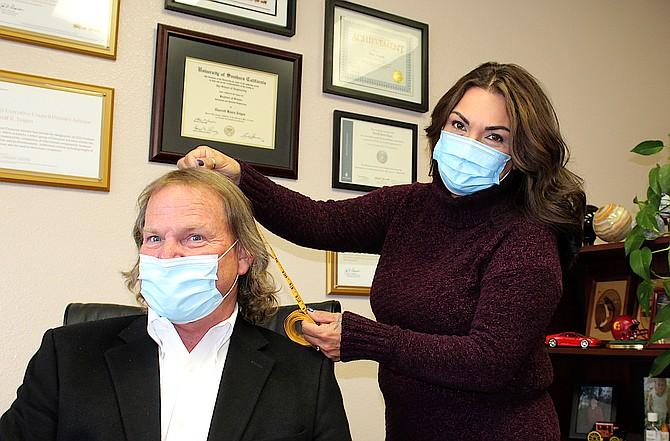 Wells Fargo Advisers Senior Vice President Investments Thor Teigen has his hair measured by Fr8tas Salon owner Norma Freitas.