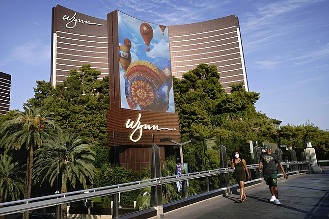 People walk along a pedestrian bridge near the Wynn Las Vegas hotel-casino on Sept. 17. (Photo: John Locher/AP, file)