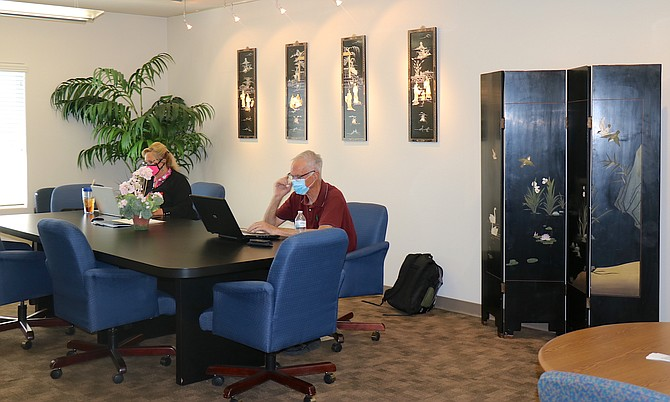 Two members of The Ant Space in Sparks work inside one of the coworking space's many non-dedicated desk areas.