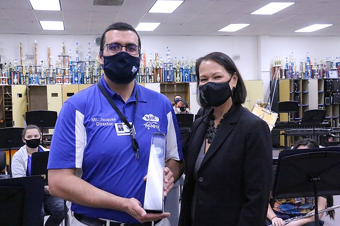 Carson High School music teacher Nicolas Jacques receives his Milken Education Award obelisk from State Superintendent of Public Instruction Jhone Ebert on Wednesday in his band room. (Photo: Jessica Garcia/Nevada Appeal)