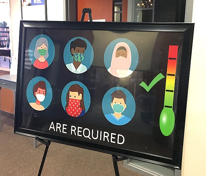 A sign at the entrance to the Douglas County Senior Center in August required visitors to wear masks. On Thursday the federal and state government said fully vaccinated people may unmask in most circumstances.